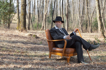 hombre con sombrero: man alone in the woods sitting on a vintage armchair
