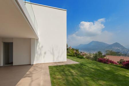 cielos abiertos: Exter de una nueva casa, terraza con césped verde