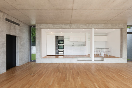 front room: Interior of modern kitchen of concrete apartment with parquet floor Stock Photo