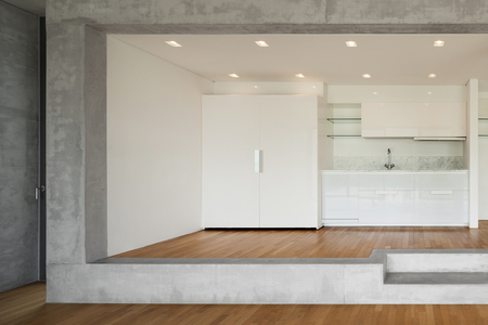 concrete floor: Interior of modern kitchen of concrete apartment with parquet floor Stock Photo