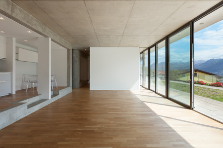 inside house: Interior of modern kitchen of concrete apartment with parquet floor Stock Photo