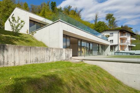 Hormigón: Exterior de una arquitectura moderna, casa de concreto con el césped verde