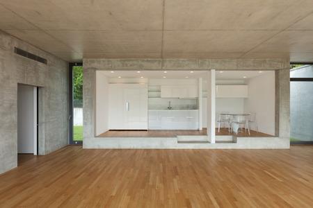 Interno di cucina moderna di appartamento in cemento con pavimento in parquet