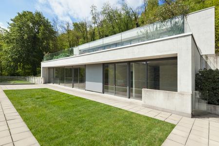 Fachada: arquitectura moderna exterior, casa de concreto con el césped verde