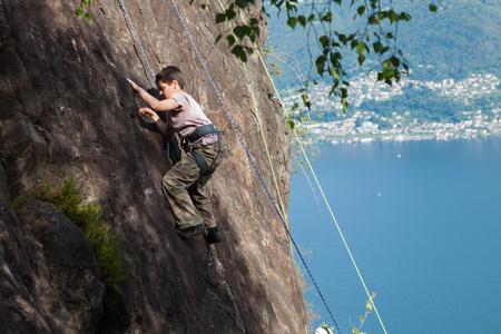 niño trepando: niño se sube en la pared de roca, al aire