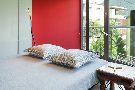 double bed: Interior of a studio apartment, double bed, red wall