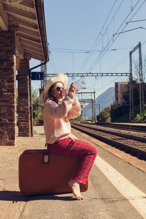 railroads: little girl waiting for the train in a deserted station Stock Photo