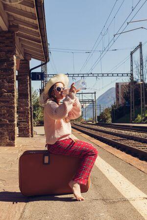 ferrocarril: niña esperando el tren en una estación desierta Foto de archivo