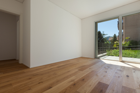 Interior of empty apartment, wide room with parquet floor