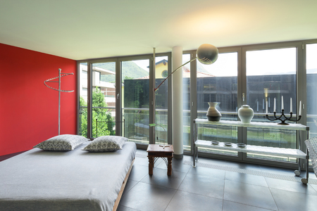 double rooms: Interior of a studio apartment, double bed, red wall