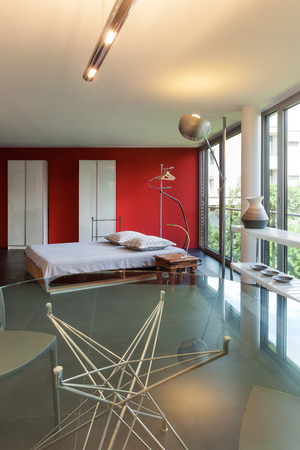double glass: Interior of a studio apartment, double bed and glass table Stock Photo