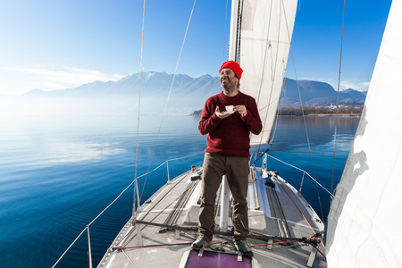 adult cruise: man makes a coffee break aboard his sailboat