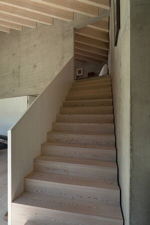 chalet: Interior of a modern chalet in cement, wooden staircase Stock Photo