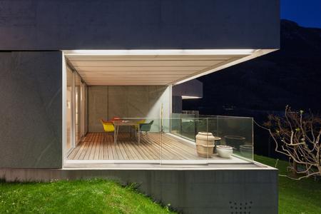 Architectuur modern design, betonnen huis, verlicht terras 's nachts