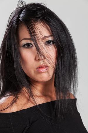 messy hair: Elegant Asian woman in studio Stock Photo