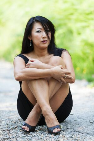 cross street with care: Asian woman sitting cross-legged in the dirt road