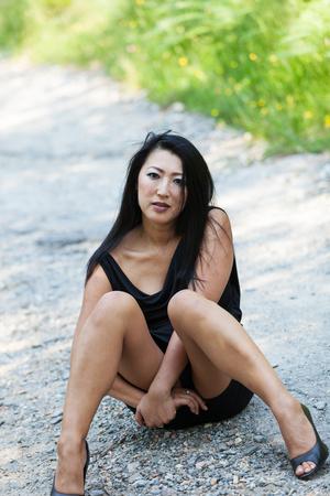 cabello negro: Asia mujer sentada con las piernas cruzadas en el camino de tierra