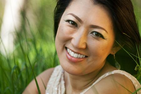 Aziatische vrouw zittend in de wei