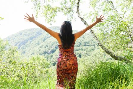 vida natural: mujer elegante con los brazos abiertos en el bosque