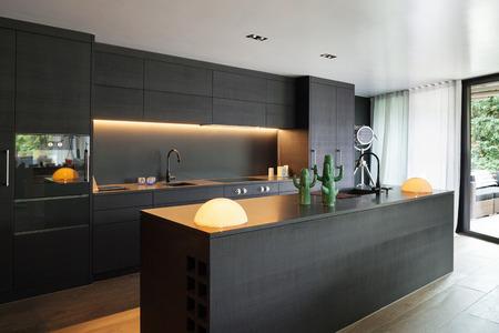 Moderne keuken met zwarte meubels en een houten vloer Stockfoto