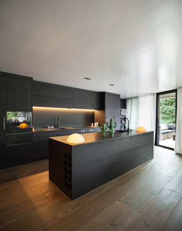 Modern kitchen with black furniture and wooden floor Reklamní fotografie