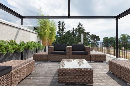 Vista de un patio moderno, con cómodos muebles de jardín