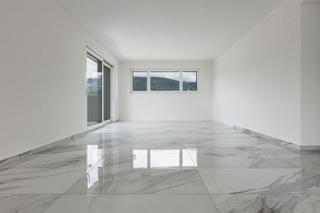 Wnętrze pustego mieszkania, szeroki pokój z marmurową podłogą