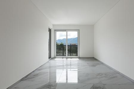 Interno di un appartamento vuoto, ampia sala con pavimento in marmo