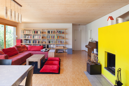 fireplace living room: Living room of an eco house, red divan and fireplace