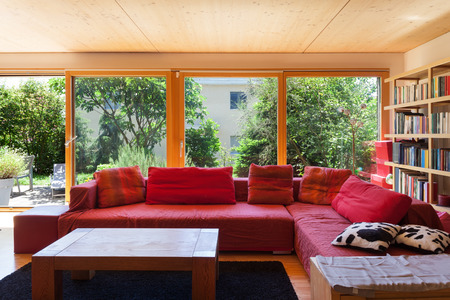 Living room of an eco house, red divan Stock Photo