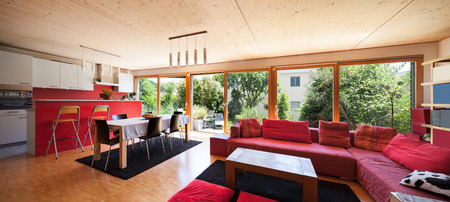 divan: Living room of an eco house, red divan and kitchen Stock Photo