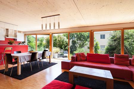 divan: sala de estar de una casa ecológica, diván rojo y cocina