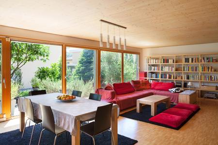 Woonkamer van een ecohuis, eettafel en rode divan
