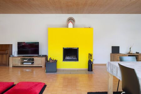 fireplace living room: Interior of an eco house, living room with yellow fireplace Stock Photo