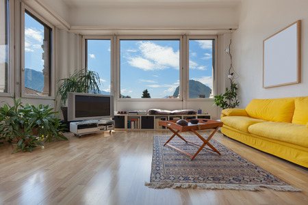 apartment living: living room of old apartment, yellow divan and wooden floor