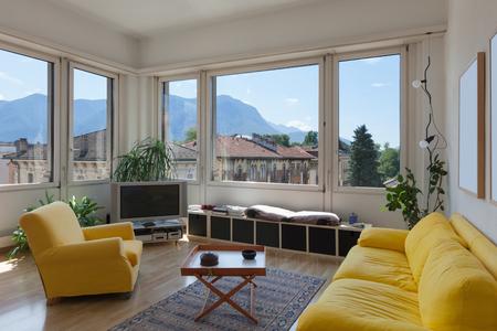 divan: salón de viejo apartamento, diván amarillo y suelo de madera