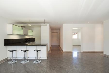 Interno di un appartamento vuoto, ampio soggiorno con cucina, pavimento in marmo