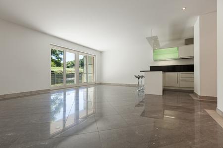 Interieur van lege flat, ruime living met open keuken, marmeren vloer Stockfoto