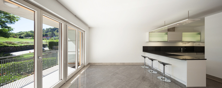 Interior of empty apartment, wide room with kitchen, marble floor
