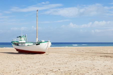 Vissersboten strandde op het strand bij eb