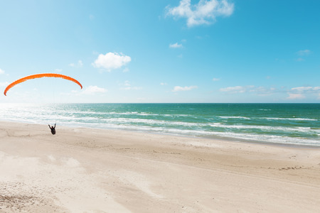 Paragliding on the deserted beach, unspoiled nature Stock Photo