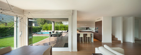 Luxe interieur, grote open ruimte, veranda en uitzicht op de tuin vanuit de ramen