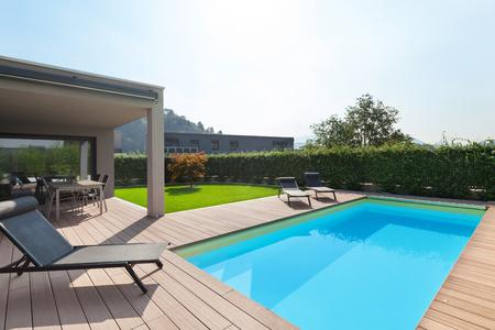 modern huis met zwembad, ligstoelen zon bij het zwembad