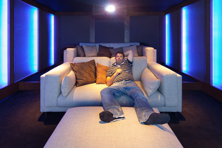home theater: Man watching a movie in the home theater, luxury interior