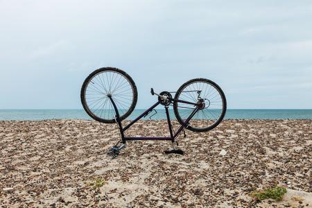 cabeza abajo: bicicleta boca abajo en la playa