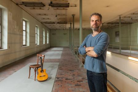silla de madera: Retrato de un músico con una guitarra