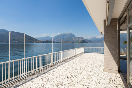 Panoramic view from the balcony of an old penthouse, lake and mountains Stock fotó