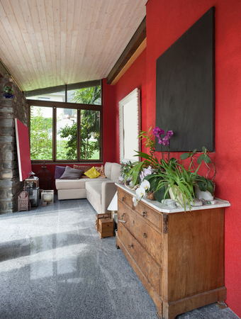 divan: Interior, terraza con cómodo sofá, la pared roja Foto de archivo