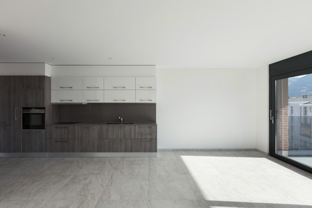 Interior of empty apartment, wide room with kitchen, tiled floor