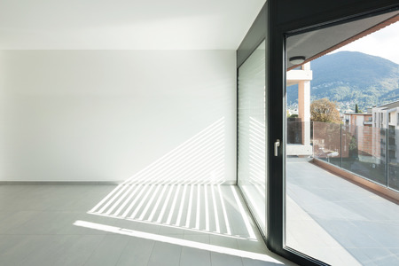 white interior: Interior of empty apartment, wide room with windows, tiled floor Stock Photo